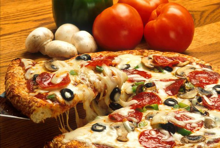 A supreme pizza with tomato sauce, cheese, pepperoni, peppers, olives, and mushrooms
