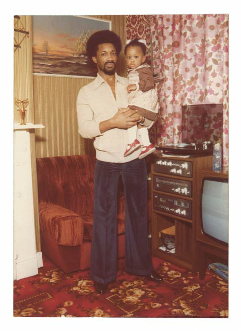 Denford Thomas, founder of Huddersfields Turbo Charge sound system, at home with his daughter, Huddersfield, 1981| Courtesy Denford Thomas & Sound System Culture Project
