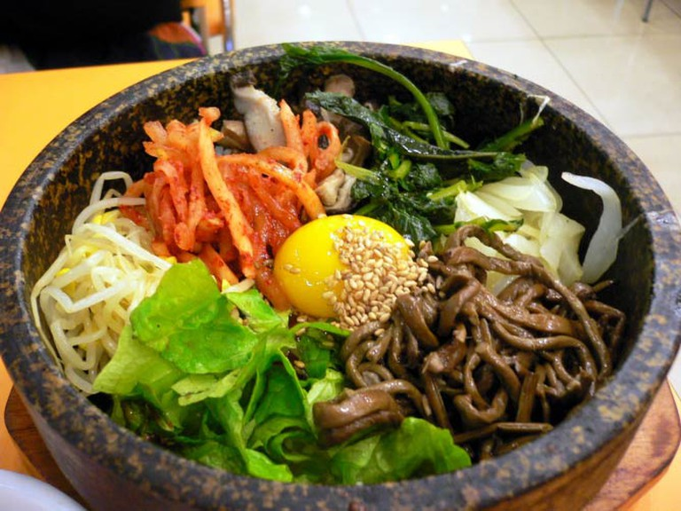 Bimbimbap is served with egg, lettuce, bean sprouts, seaweed, rice, and kimchi