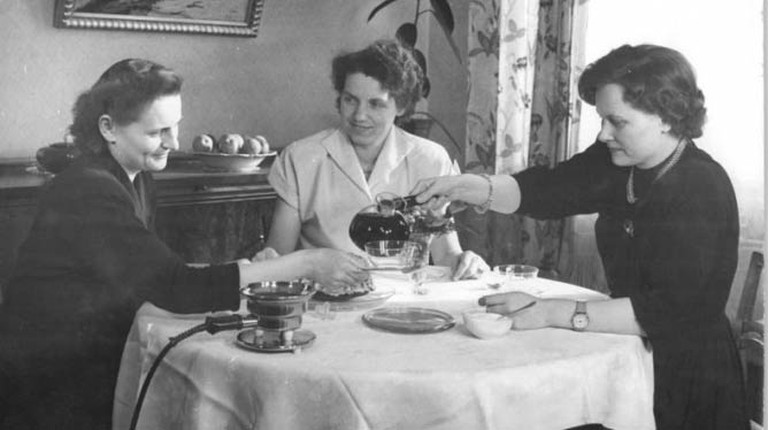Three ladies sit around a table enjoying afternoon coffee