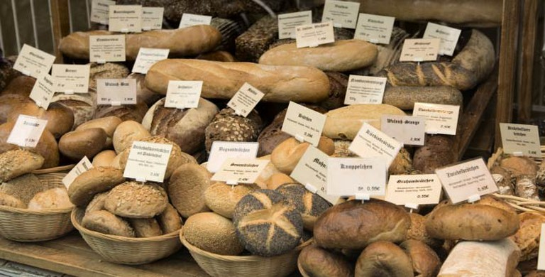 A variety of bread and loaves for sale line a table top