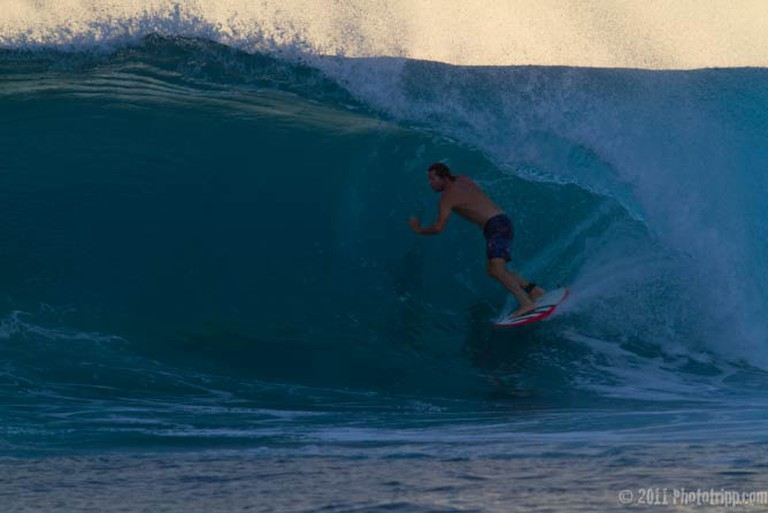 Surfer getting a late afternoon barrel at Macaronis in Indonesia