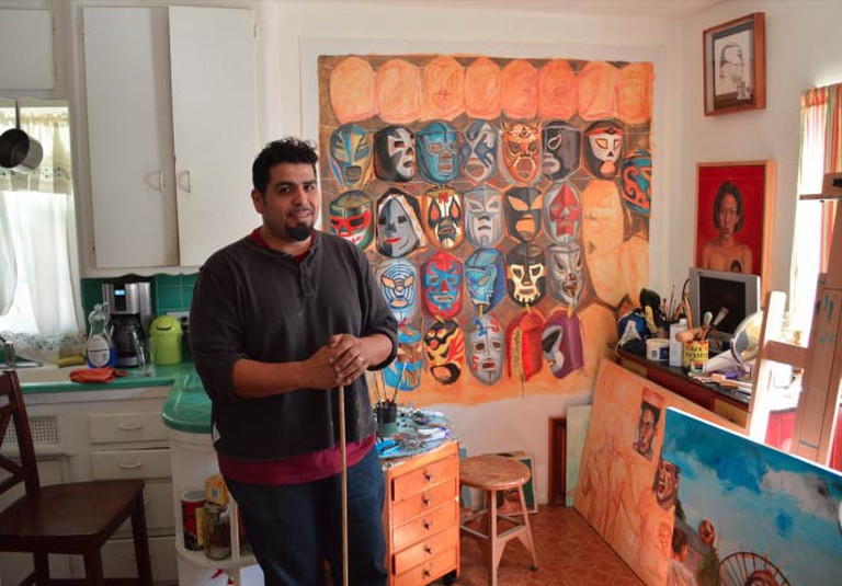 Sergio Teran in his kitchen workspace, and behind an unfinished 43 Ayotzinapa masks painting. Photo by Michael Reyes