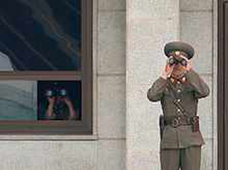 Tourism in North Korea – Korean Soldiers observing the South Korean side of the DMZ   © Edward N. Johnson