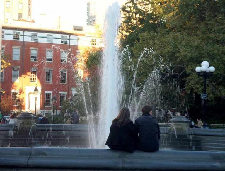 A couple enjoys the fountain at Washington Square Park