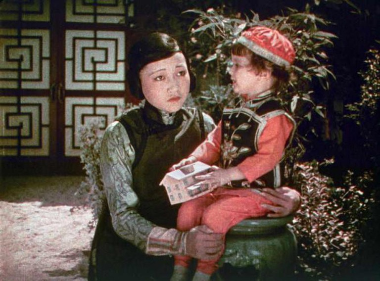 A colourful image of a Chinese woman looking concerned as she holds a young boy.
