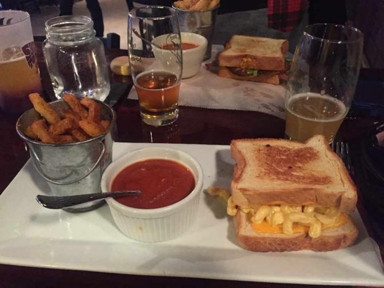 Mac and cheese grilled cheese sandwich with tomato soup and fries.