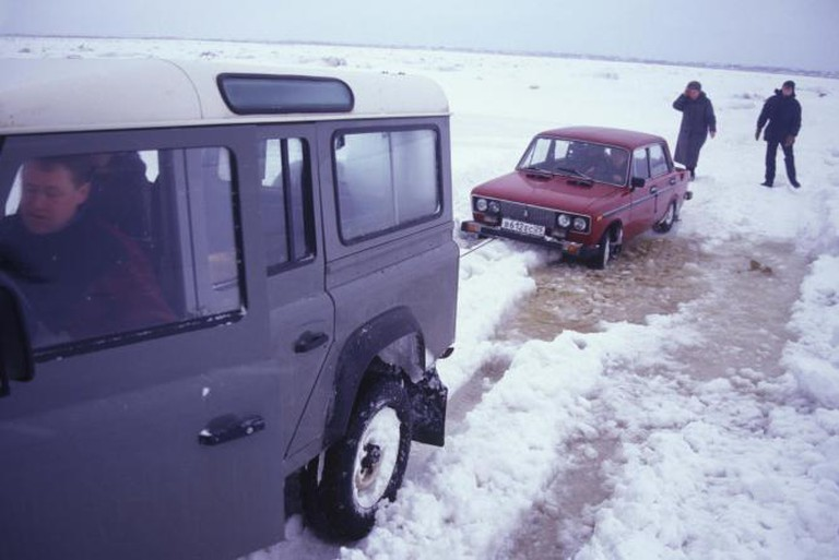 """Car being pulled from icy slush on """"frozen"""" surface of Mezen River between Mezen and Kamenka. Photograph: March 8, 2000."""
