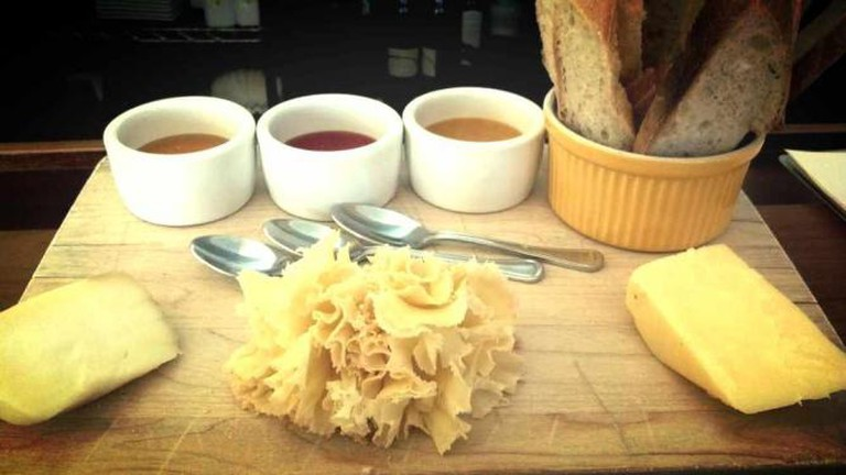 A board of cheese, oils and mustard sit on a table at a Tria restaurant