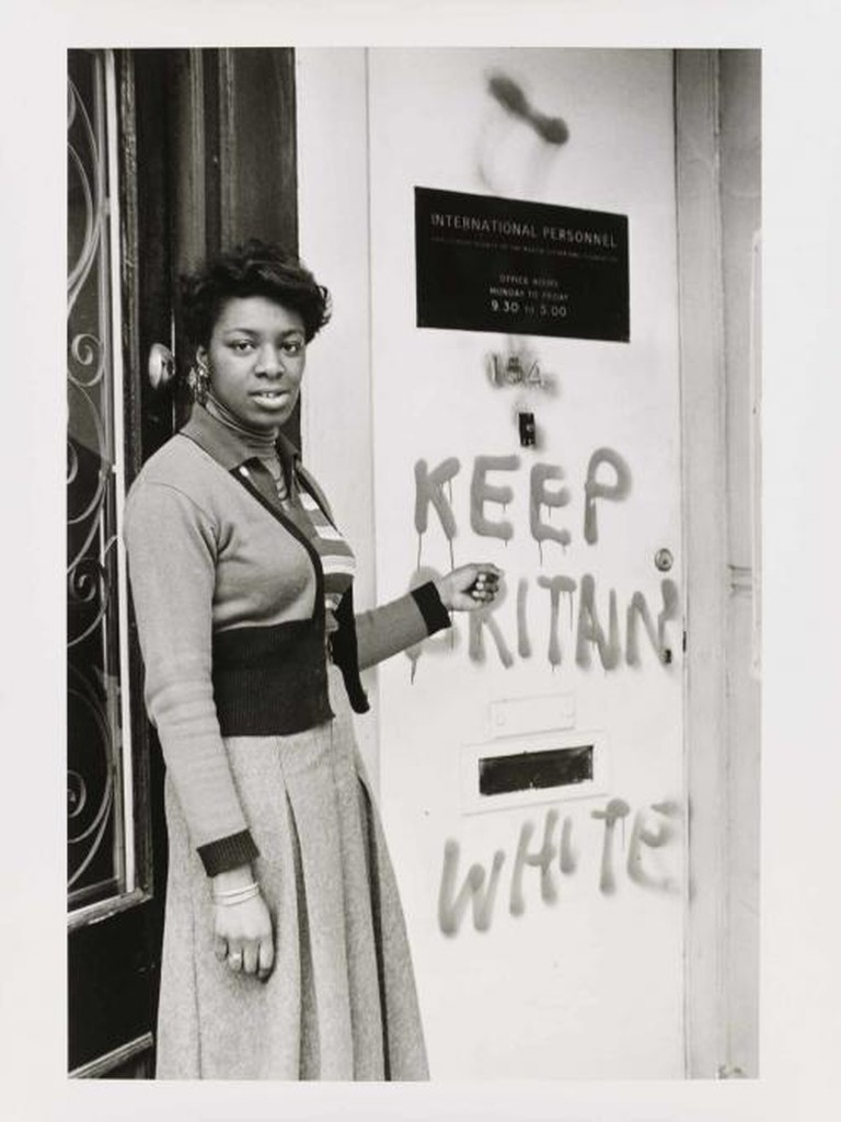 Neil Kenlock, 'Untitled [Young lady points to 'Keep Britain White' graffiti at the International Personnel training centre in Balham]', 1974. © Neil Kenlock/ Victoria and Albert Museum, London. Supported by the National Lottery through the Heritage Lottery Fund.
