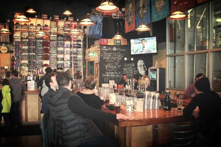 A shot of beer drinkers sitting at the Yards Brewing Company tasting room watching sports on TV.