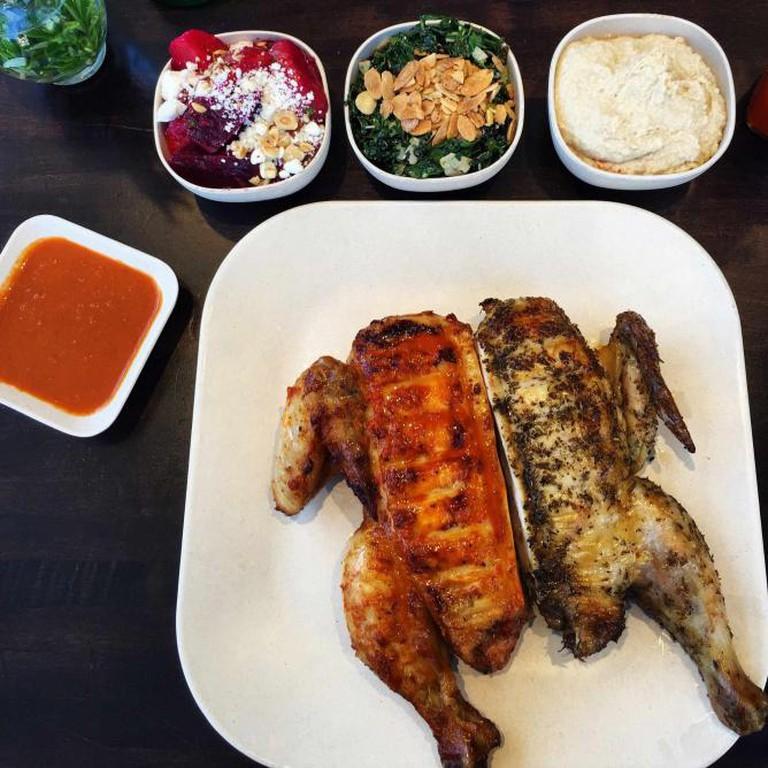 Half Mediterranean half peri peri chicken with sides of kale salad, hummus and roasted beets | ©Lauryn D'Angelo