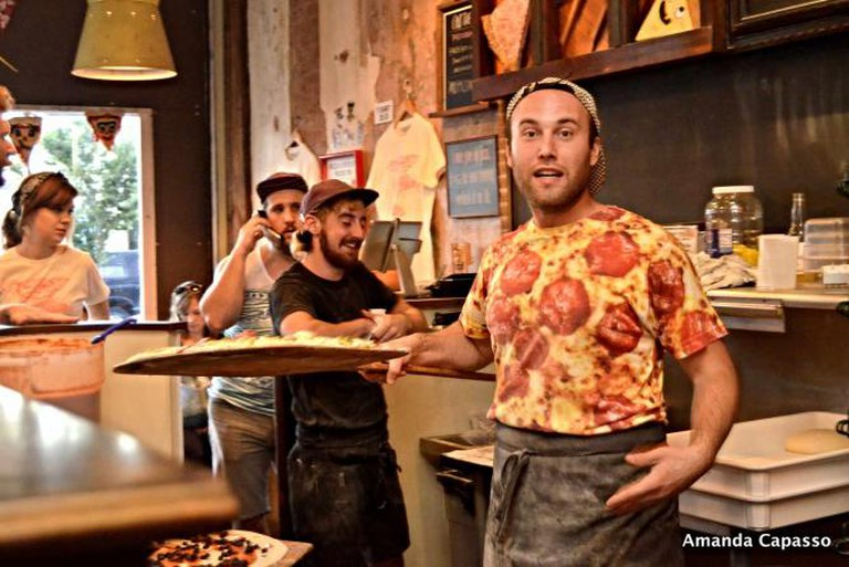 Servers take pizzas out of the oven at Pizza Brain.