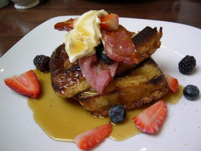 French Toast topped with maple syrup and bacon
