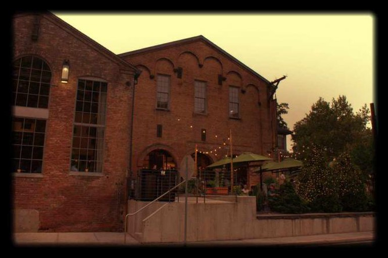 The romantic, tree-lined patio is seen from the street at Woodberry Kitchen which is restored from an old mill.