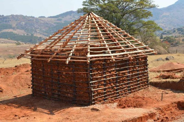 Swaziland home being constructed wood frame with rocks placed inside and will be plasterered with mud | © Jon Sojkowski