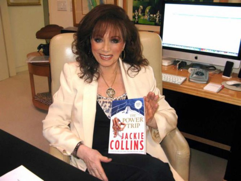 Jackie Collins holding up her novel | © Cyotethndr/WikiCommons