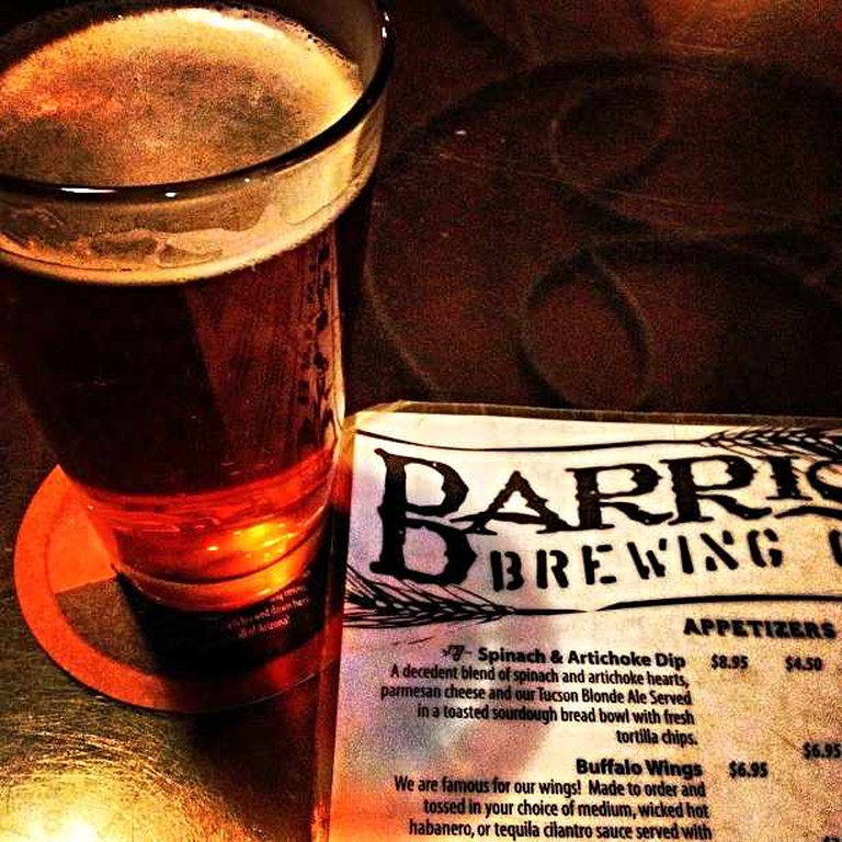 One of the 12 drafts sits by Barrio Brewing Co's menu.