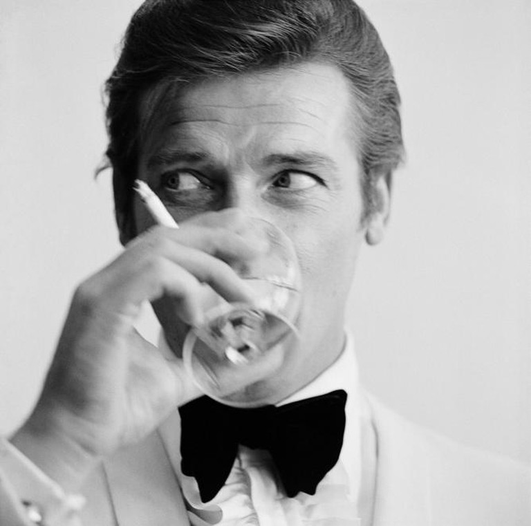 English film star Roger Moore, well known for his roles as James Bond and the Saint, downs a martini   Courtesy of Everyman Theatre and Getty Images.
