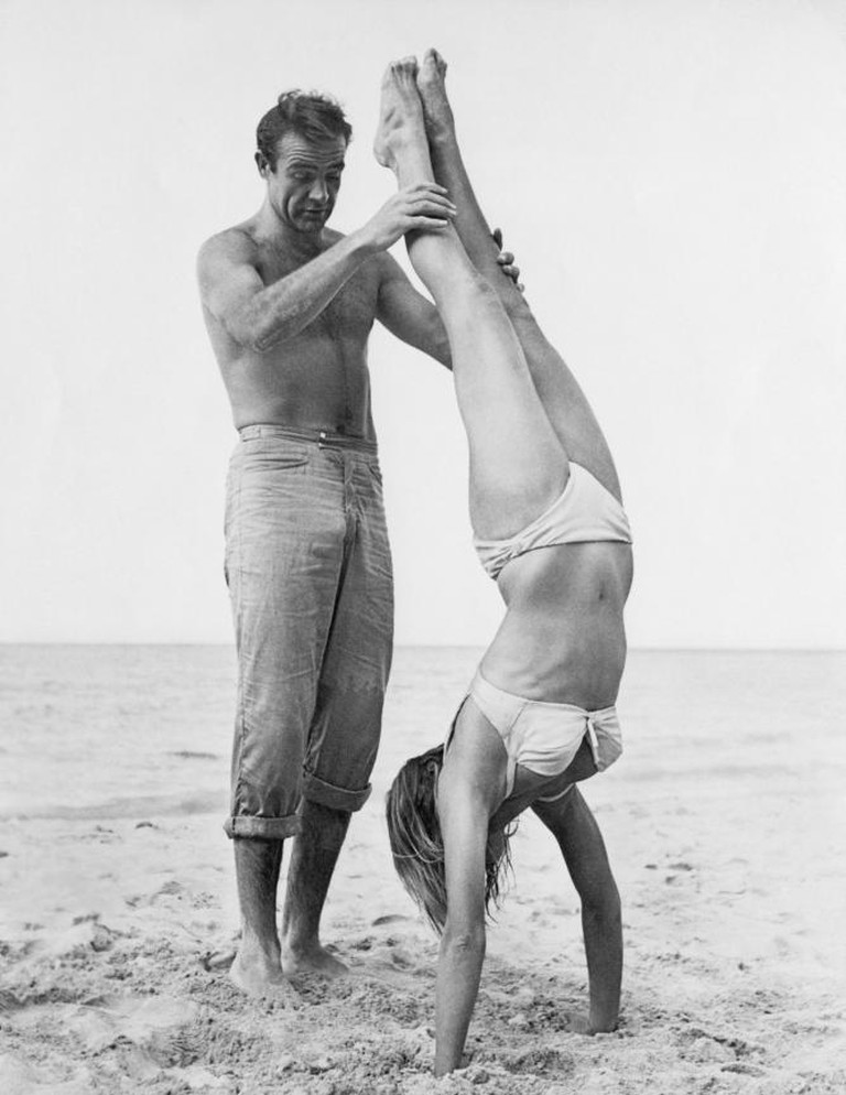Shirtless Scottish actor Sean Connery holds Swiss actor Ursula Andress while she does a handstand on a beach in a white bikini on the set of the film, 'Dr. No'   Courtesy of Everyman Theatre and Getty Images.