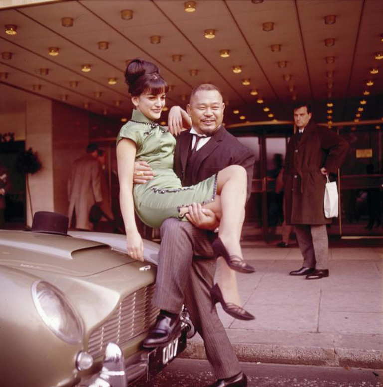 American actor, weightlifter and wrestler Harold Sakata (1920-1982) posed in character as Oddjob from the James Bond film 'Goldfinger', holding Hilton Hotel secretary Dawn Dunger in London in 1965. Sakata has one foot resting on James Bond's Aston Martin DB5   Courtesy of Everyman Theatre and Getty Images.