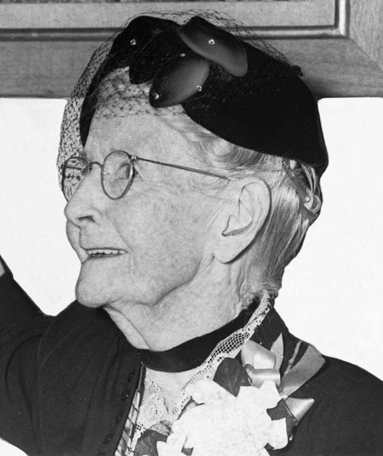 "Grandma Moses, cropped from photo of ""Grandma Moses donating her painting ""Battle of Bennington"" to Mrs. George Kuhner who accepts it for DAR."" (Photo cropped because the painting itself is most likely still copyrighted.) 