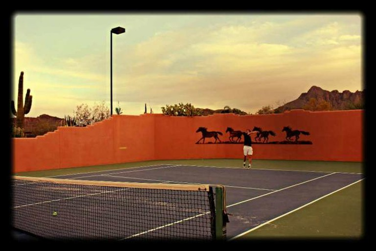The White Stallion includes many amenities like a tennis court set against the desert.