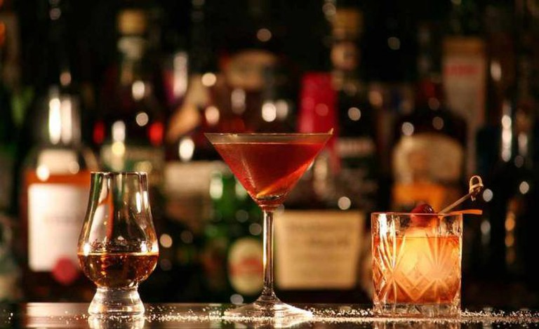 a bar with three glasses, from left to right: rum, Manhattan, tequila Old Fashioned