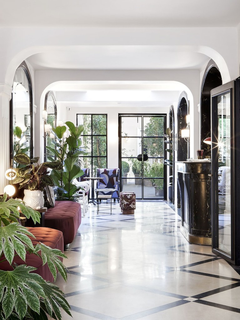 Velvet seating, potted plants and floor-to-ceiling glass doors in the lobby of Hotel Bienvenue