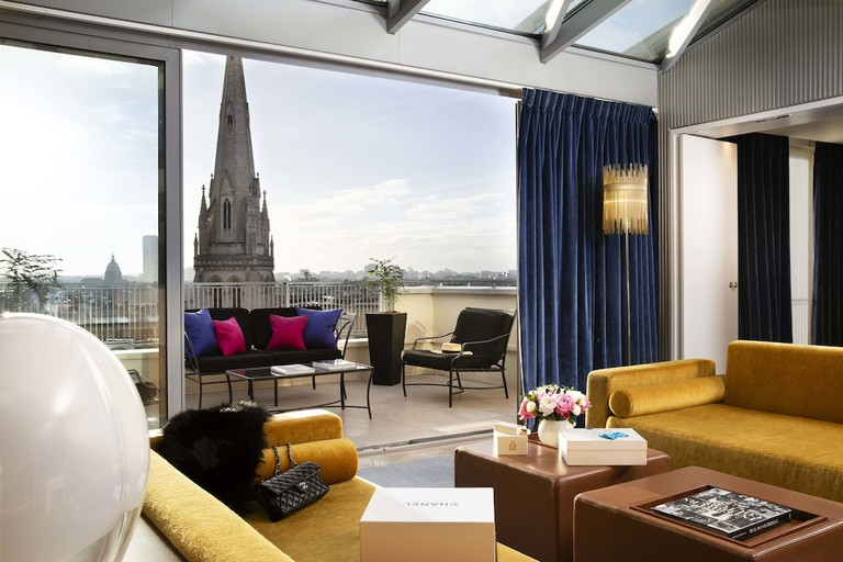 A living room with gold-coloured sofas leads out to a hotel terrace with black chairs