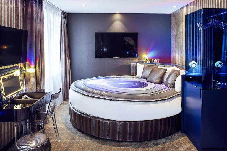 A bed with artwork of a woman taking a photo in a hotel room at Hôtel Déclic