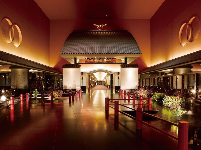 The huge entrance of Hotel Gajoen Tokyo, with glass walls and a glass roof, with a garden and staircase