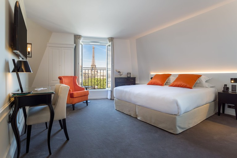 A white hotel room with a twin bed, orange armchair and desk. In the background, a large window is open with a view of the Eiffel Tower