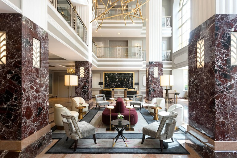 Seating area at Hotel LeVeque with marble pillars and maroon soft furnishings