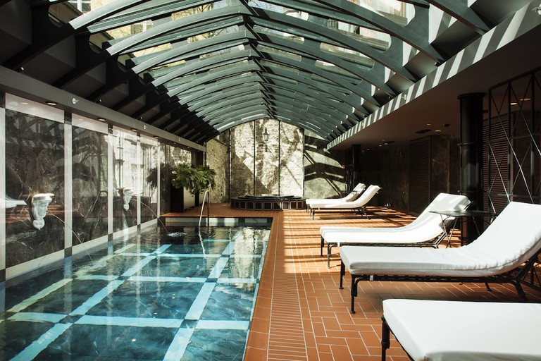 Serene private pool with lounge chairs and a plant-filled wall at Hotel Telegraaf