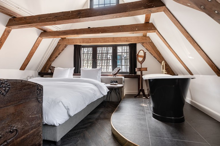 A bed and freestanding bathtub in a hotel room with wooden beams at the Craftsmen