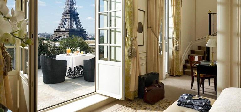 A grand living room with two sofas and two tables, with a terrace outside that overlooks the Eiffel Tower