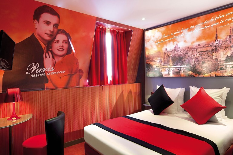 A hotel room with a bed and artwork with French phrases on the wall at Hotel Montmartre Mon Amour