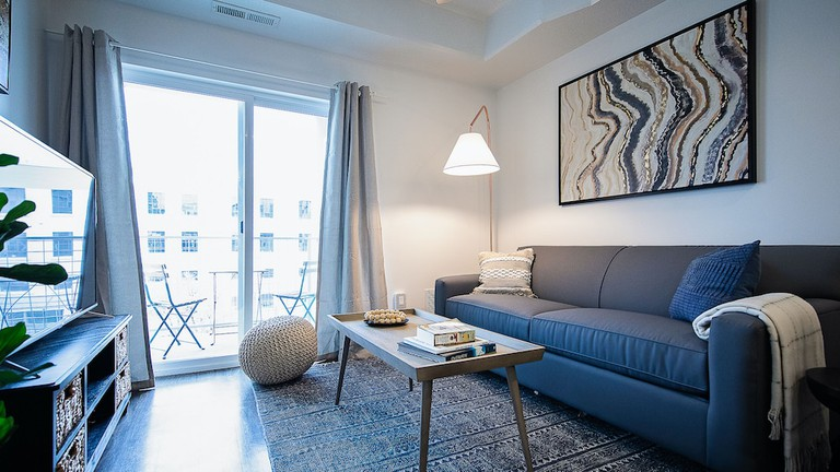 Modern living room with tall freestanding lamp and mid-century table in Kasa Salt Lake City Downtown Apartments