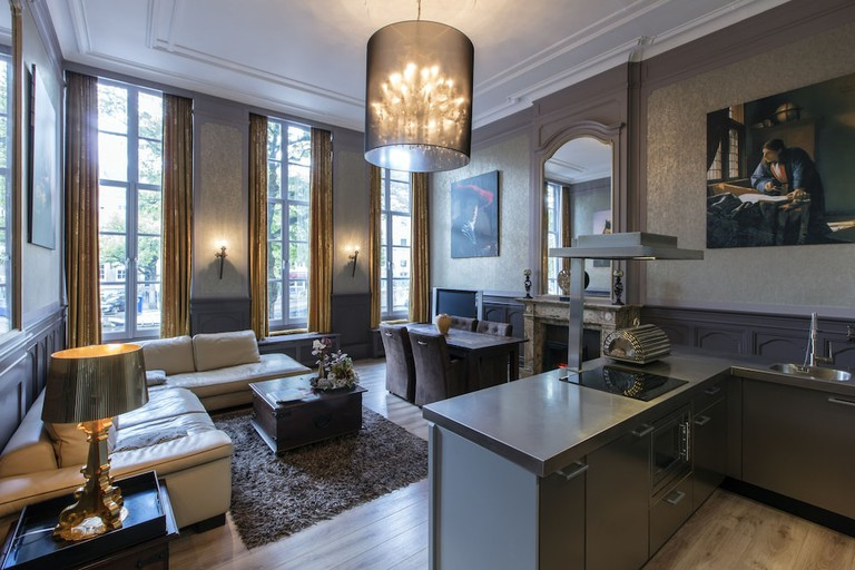 A seating area, dining table, and kitchen in a hotel room at Dutch Masters Amsterdam