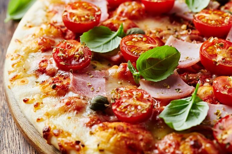 Fresh pizza with ham and cherry tomatos