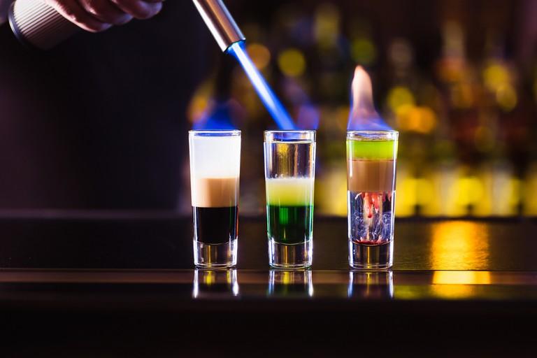 Three multi-layer burning cocktail. The bartender ignites them lighter © Goncharov_Artem / Shutterstock