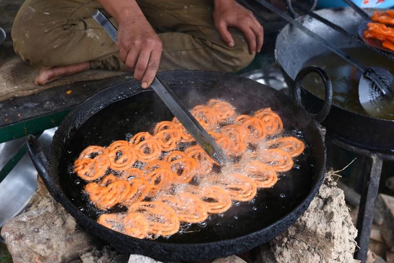 Indian jalebi sweet at a street stall, yummy street food © Singh_lens / Shutterstock