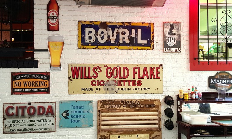 Antique enamel signs in the patio area at The Irish Bank