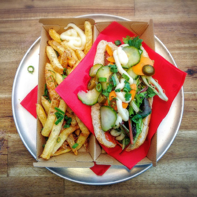 Banh Mi DOG. Wholemeal bread, homemade garlic mayonnaise, beef sausage, 24h marinated carrot, cucumber and jalapeños, coriander and cheddar cheese, served with a side of homemade chips | Courtesy of Wassup Dog