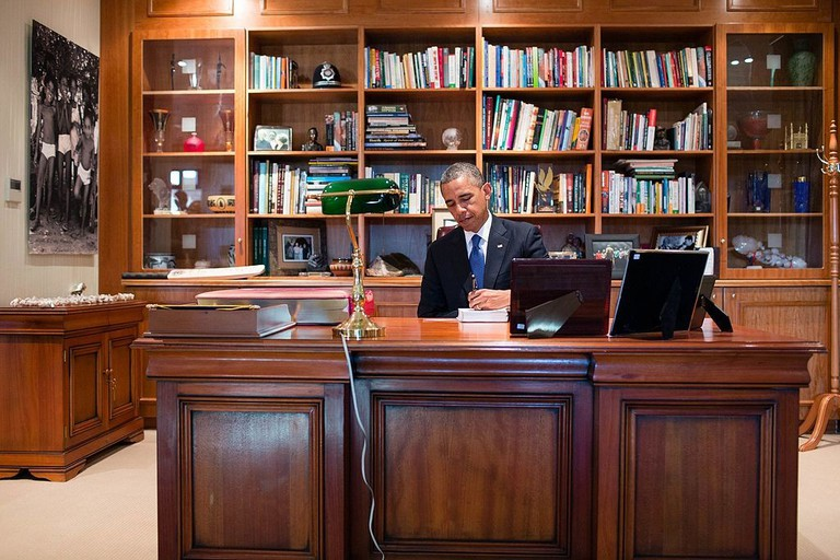 "President Barack Obama signs a copy of former South African President Nelson Mandela's book ""Conversations with Myself"" while visiting Mandela's office at the Nelson Mandela Centre of Memory in Johannesburg, South Africa, June 29, 2013 © The White House/WikiCommons"