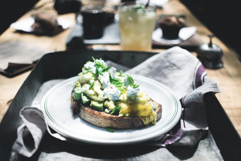 Scrambled eggs, avocado, sour cream and radish on artisan bread at HM FoodC