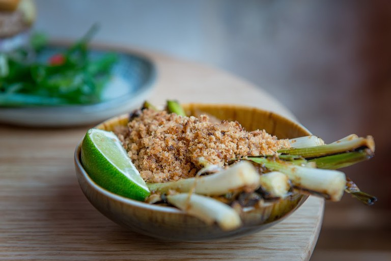 Fried green onions with peanuts and a side of lime at Tel Aviv's Fifi's Asian Food