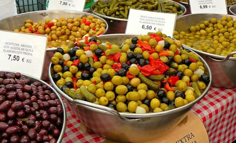 """<a href=""""https://pixabay.com/en/olives-market-drupes-mediterranean-992240/"""">Olive stall   © cocoparisienne/Pixabay</a>"""