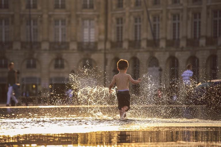 Little boy playing in Bordeaux's Water Mirror | © Eo Naya/Shutterstock